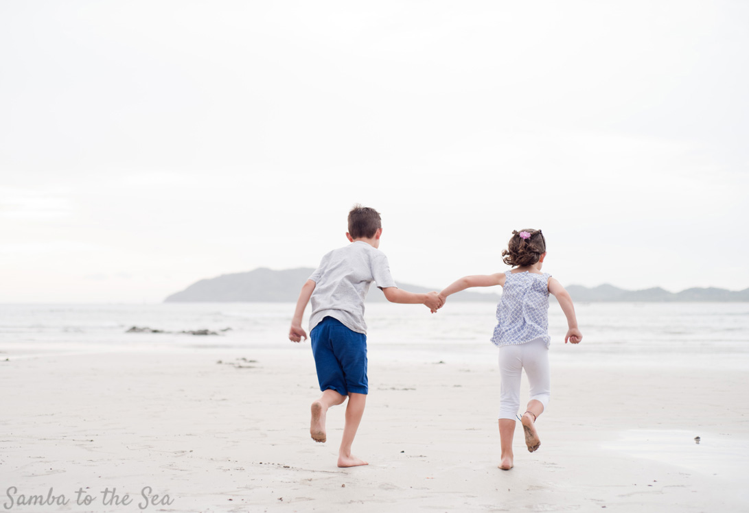 Brother and sister running down the beach holding hands in Costa Rica. Photographed by Kristen M. Brown, Samba to the Sea Photography.