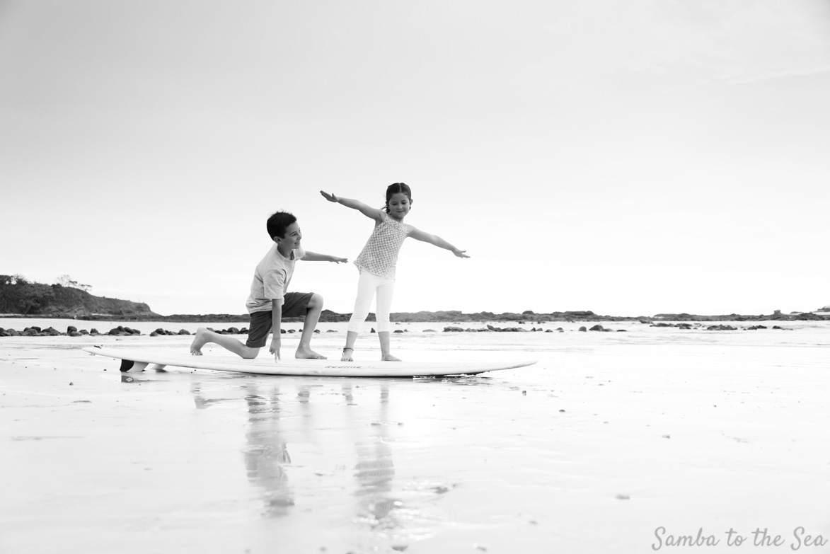 Black and white photo of siblings playing on a surfboard in Tamarindo, Costa Rica. Photographed by Kristen M. Brown, Samba to the Sea Photography.