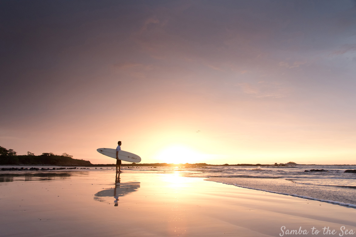 Man holding a surfboard during sunset in Tamarindo, Costa Rica. Photographed by Kristen M. Brown, Samba to the Sea Photography.