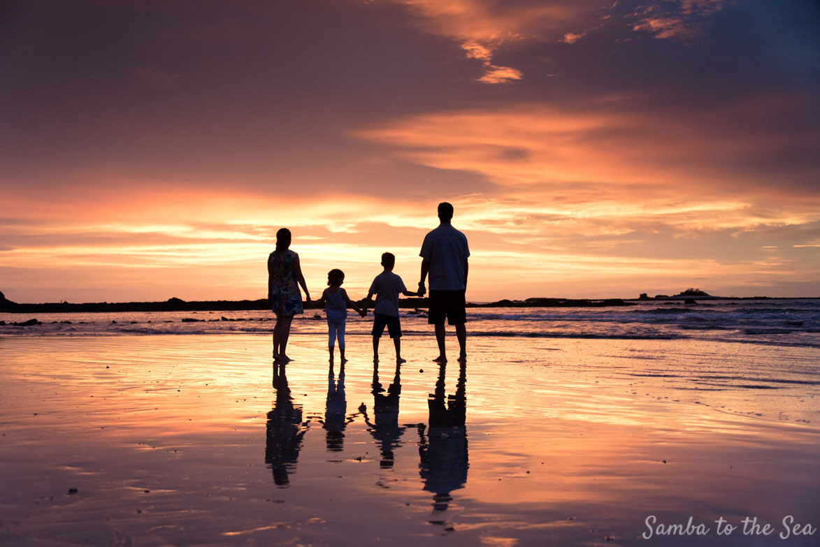 Family holding hands during sunset in Tamarindo, Costa Rica. Photographed by Kristen M. Brown, Samba to the Sea Photography.