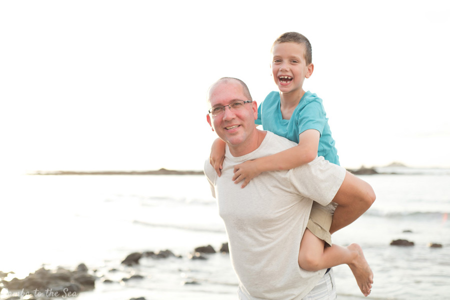 Father giving his son a piggy back ride during family photos on the beach in Tamarindo, Costa Rica. Photographed by Kristen M. Brown, Samba to the Sea Photography.