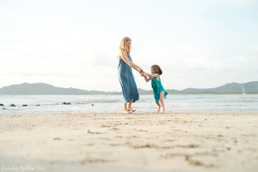 Mom and daughter twirling on the beach in Tamarindo, Costa Rica. Photographed by Kristen M. Brown, Samba to the Sea Photography.