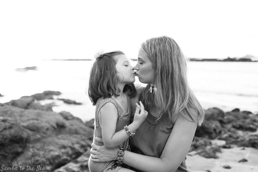 Young daughter giving her mom a kiss during family photos in Tamarindo, Costa Rica. Photographed by Kristen M. Brown, Samba to the Sea Photography.