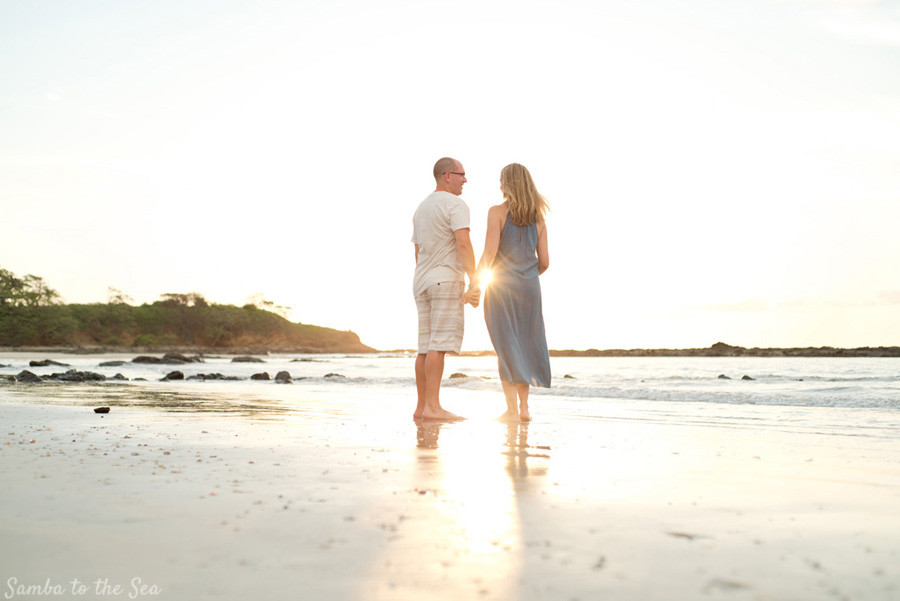 Sun star bursting through husband and wife during family portraits in Tamarindo, Costa Rica. Photographed by Kristen M. Brown, Samba to the Sea Photography.