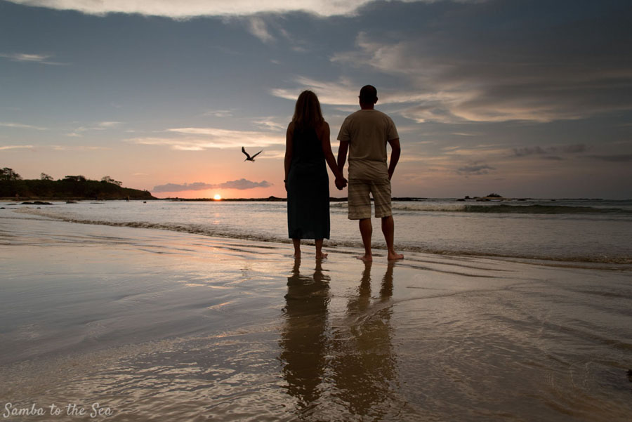 Husband and wife watching sunset on the beach in Tamarindo, Costa Rica. Photographed by Kristen M. Brown, Samba to the Sea Photography.