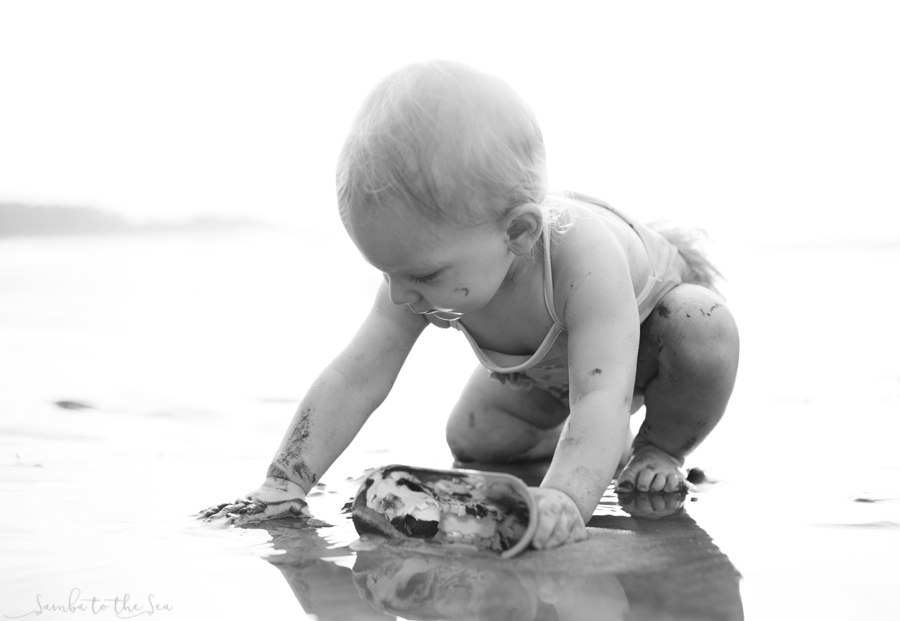 Black and white photo of baby girl playing in the sand for the first time in Tamarindo, Costa RIca. Photographed by Kristen M. Brown, Samba to the Sea Photography.