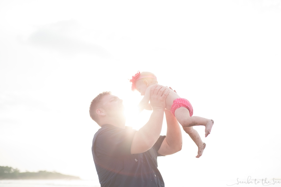 Golden hour photo of father holding his baby girl on the beach in Costa Rica. Photographed by Kristen M. Brown, Samba to the Sea Photography.