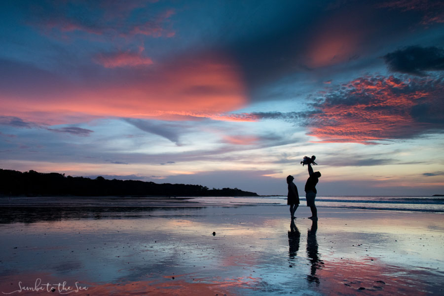 Gorgeous sunset silhouette of father throwing his baby girl in the air in Tamarindo, Costa Rica. Photographed by Kristen M. Brown, Samba to the Sea Photography.