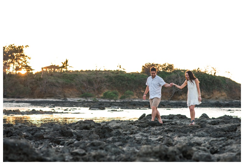 Fiancé leading his girlfriend over the low tide rocks in Tamarindo, Costa Rica. Photographed by Kristen M. Brown, Samba to the Sea Photography.