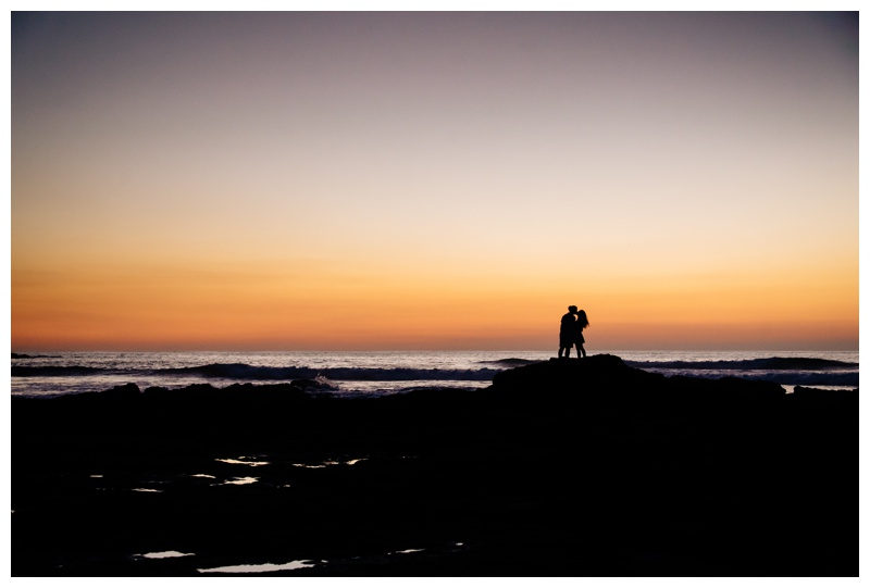 Silhouette of couple about to kiss on the low tide rocks in Tamarindo, Costa Rica. Photographed by Kristen M. Brown, Samba to the Sea Photography.