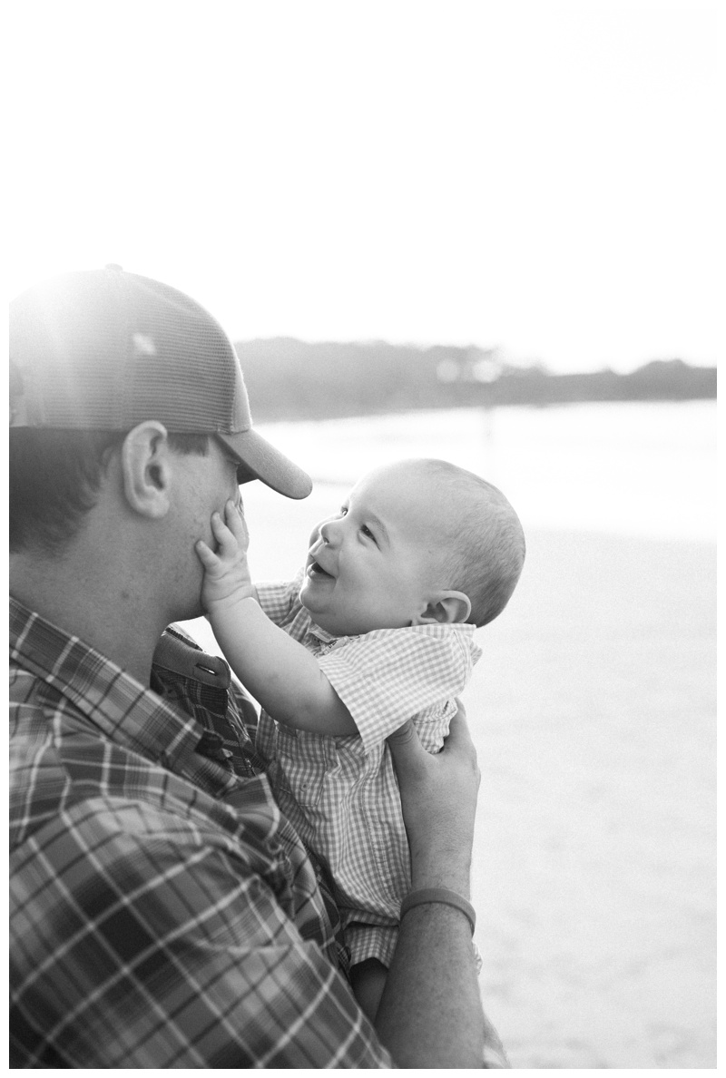 Baby boy playing with his father's hat during family photos on the beach in Tamarindo, Costa Rica. Photographed by Kristen M. Brown, Samba to the Sea Photography.