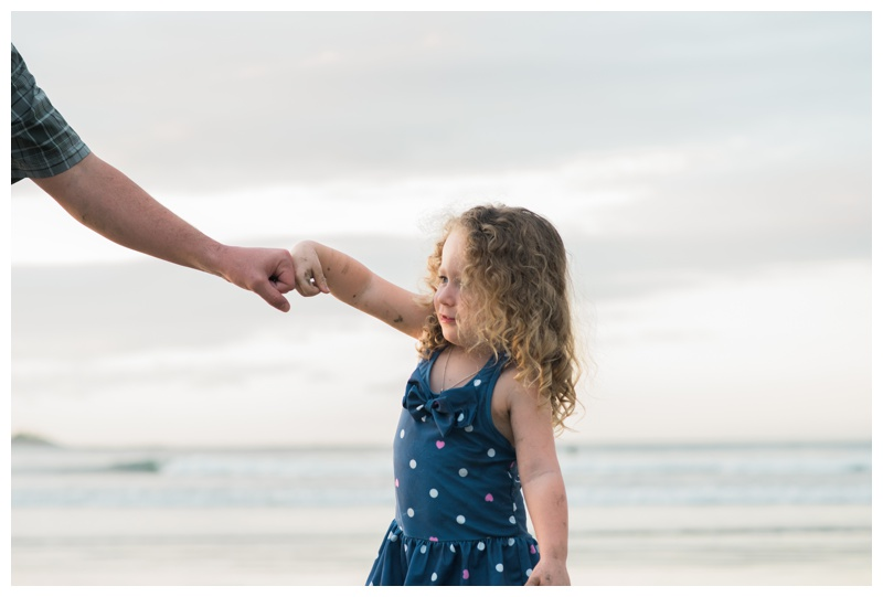 Young girl pounding fists with her dad during family photos in Costa Rica. Photographed by Kristen M. Brown, Samba to the Sea Photography.