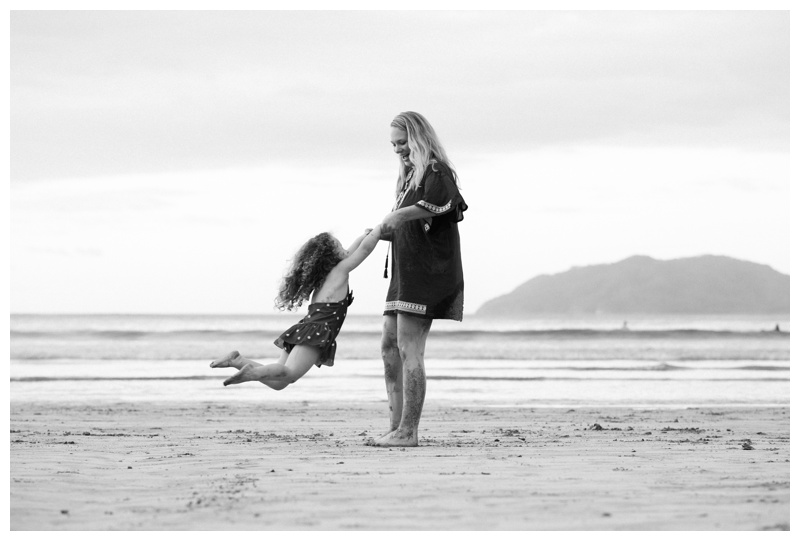 Mom spinning her daughter in the air on the beach in Tamarindo, Costa Rica. Photographed by Kristen M. Brown, Samba to the Sea Photography.