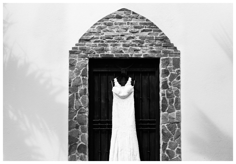 Black and white photo of bohemian wedding dress by Pronovias hanging on an iron gate at Casa de las Tortugas in Playa Langosta, Costa Rica. Photographed by Kristen M. Brown, Samba to the Sea Photography.
