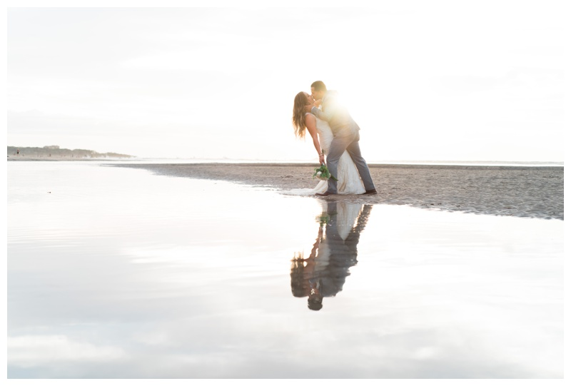 Reflection of groom dipping his bride after their Costa Rican beach wedding in Tamarindo. Photographed by Kristen M. Brown, Samba to the Sea Photography.