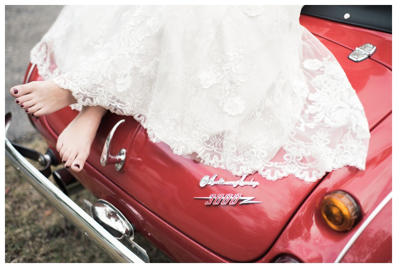 Bridal portraits with a classic convertible Austin Healey in Savannah, Georgia. Bride is wearing a gorgeous dress by Maggie Sottero Designs and veil by Adele Amelia Bridal, available at Ivory & Beau Bridal Boutique in Savannah, GA. Photographed by Kristen M. Brown, Samba to the Sea Photography.