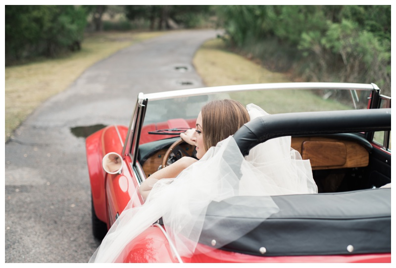 Bride driving a classic red Austin Healey convertible. Bride is wearing a gorgeous dress by Maggie Sottero Designs and veil by Adele Amelia Bridal, available at Ivory & Beau Bridal Boutique in Savannah, GA. Photographed by Kristen M. Brown, Samba to the Sea Photography.