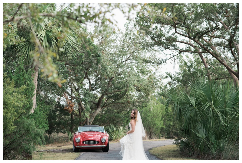 Bride walking down a curved road towards her classic red convertible in Savannah, Georgia. Bride is wearing a gorgeous dress by Maggie Sottero Designs and veil by Adele Amelia Bridal, available at Ivory & Beau Bridal Boutique in Savannah, GA. Photographed by Kristen M. Brown, Samba to the Sea Photography.