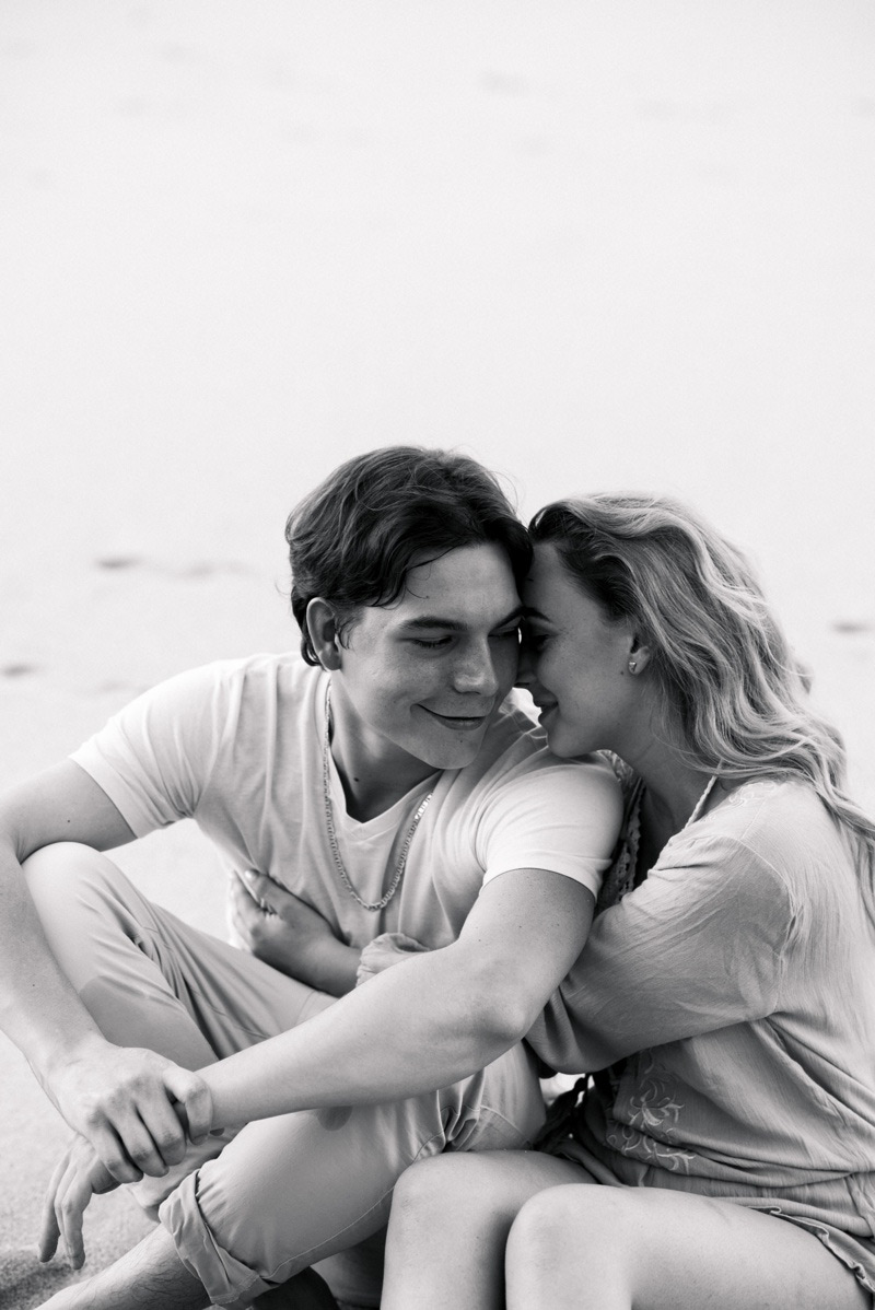 Black and white photo of girlfriend cuddling up to her boyfriend on the beach in Playa Conchal, Costa Rica. Photographed by Kristen M. Brown, Samba to the Sea Photography.