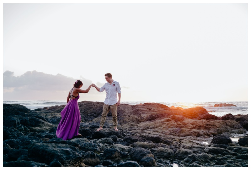 Groom leading his bride on the low tide rocks in Playa Langosta, Costa Rica. Bride is wearing a purple wedding dress. Photographed by Kristen M. Brown, Samba to the Sea Photography.