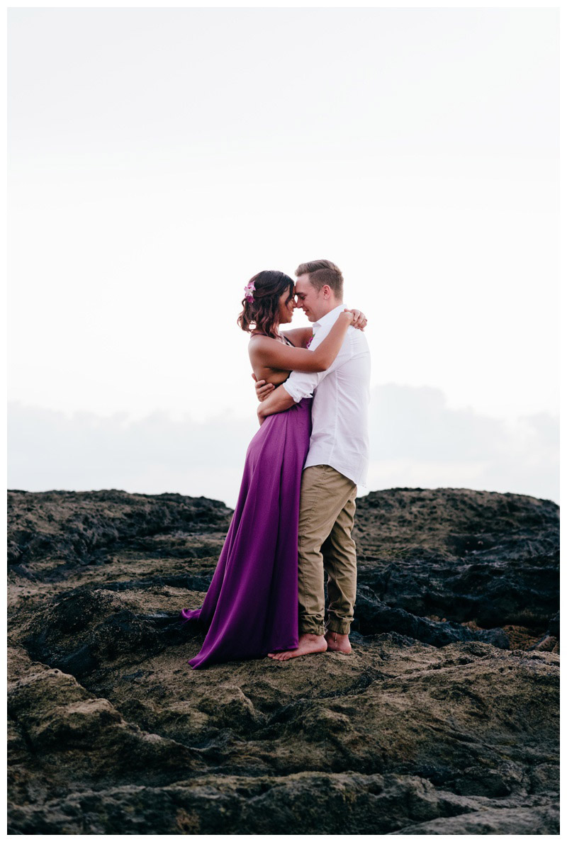 Bride and groom embracing on the low tide rocks in Playa, Langosta, Costa Rica. Bride is wearing a purple wedding dress. Photographed by Kristen M. Brown, Samba to the Sea Photography.