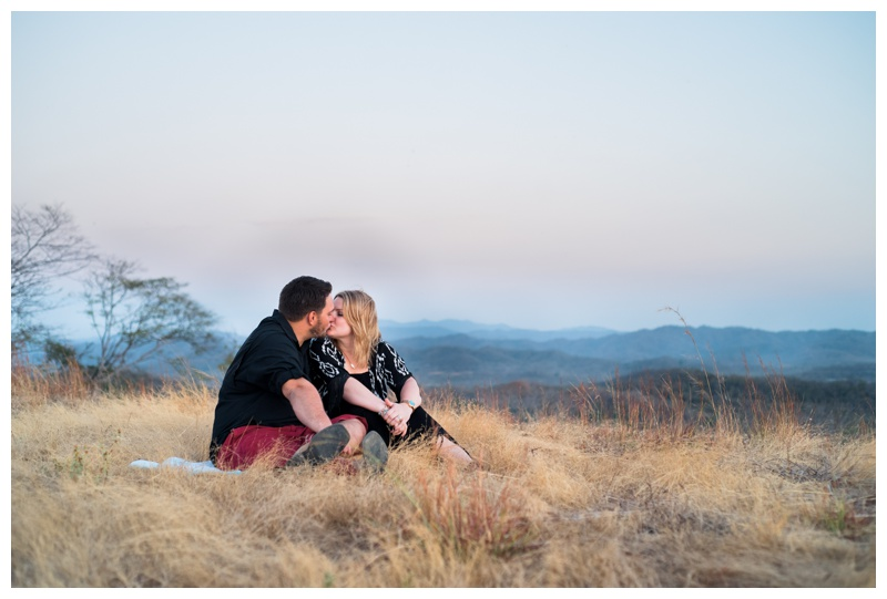 Couple kissing at the lookout in Tamarindo with a gorgeous mountain and ocean view. Photographed by Kristen M. Brown, Samba to the Sea Photography.