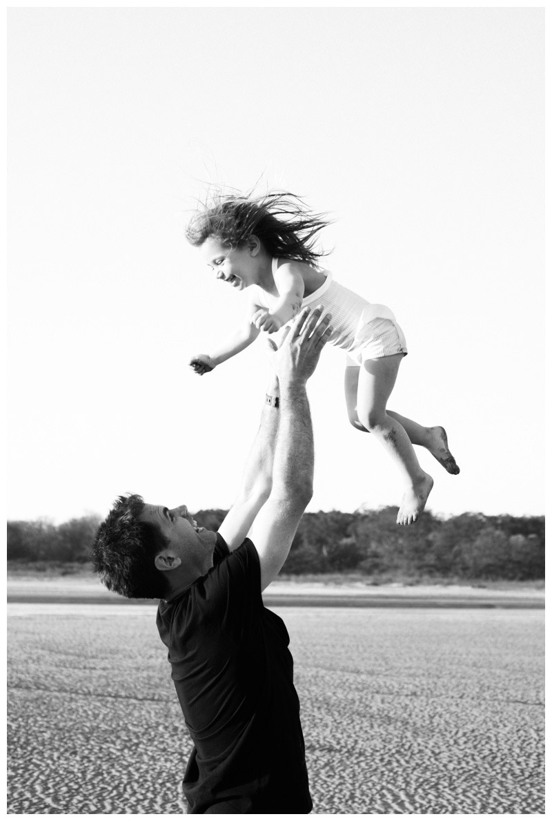Black and white image of father throwing his daughter in the air on the beach in Tamarindo, Costa Rica. Photographed by Kristen M. Brown, Samba to the Sea Photography.