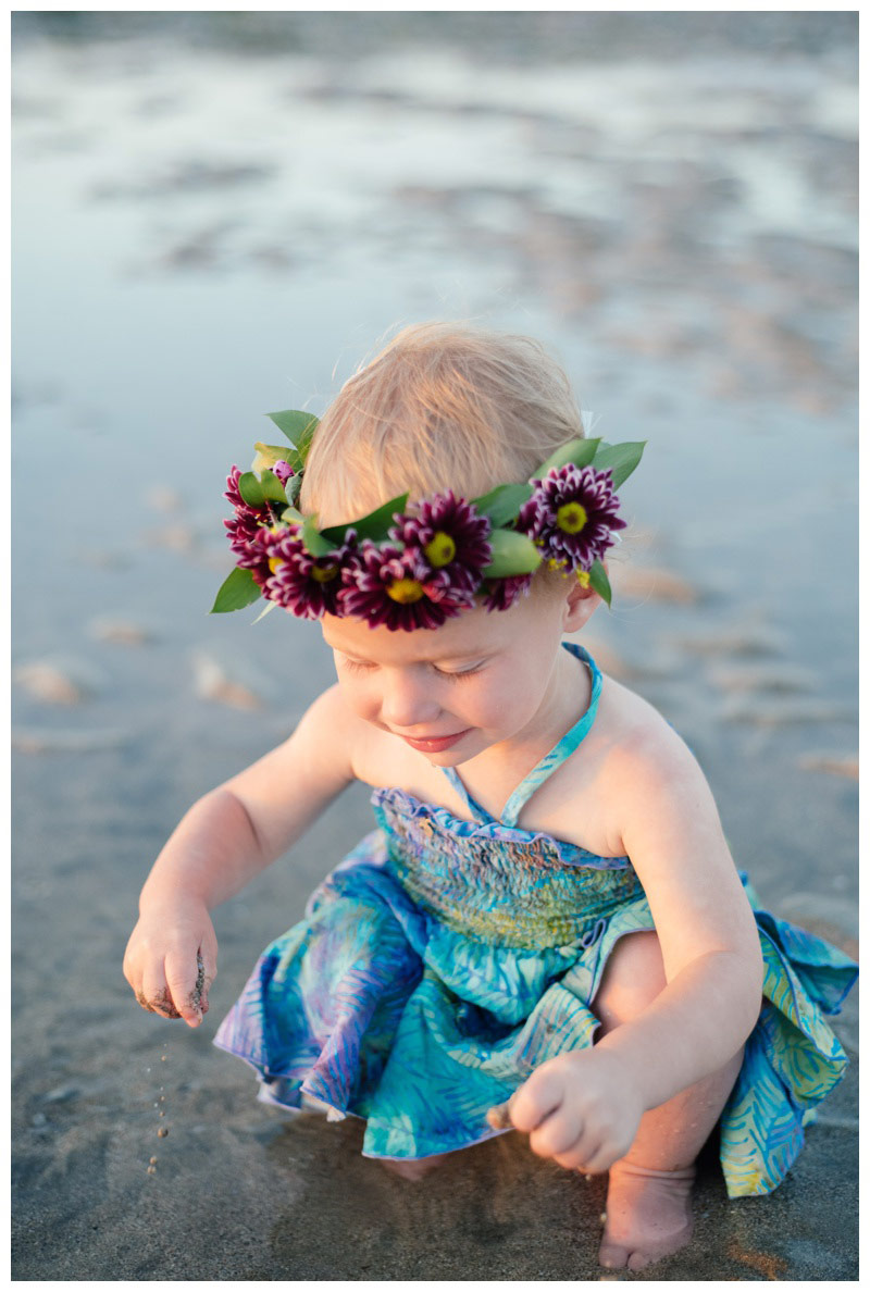 Toddler playing in the wet sand in Costa Rica. Toddler is wearing a purple flower crown. Photographed by Kristen M. Brown, Samba to the Sea Photography.