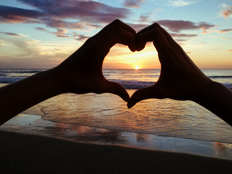Hands in the shape of a heart during sunset in Playa Avellanas, Costa Rica. Photographed by Kristen M. Brown, Samba to the Sea.