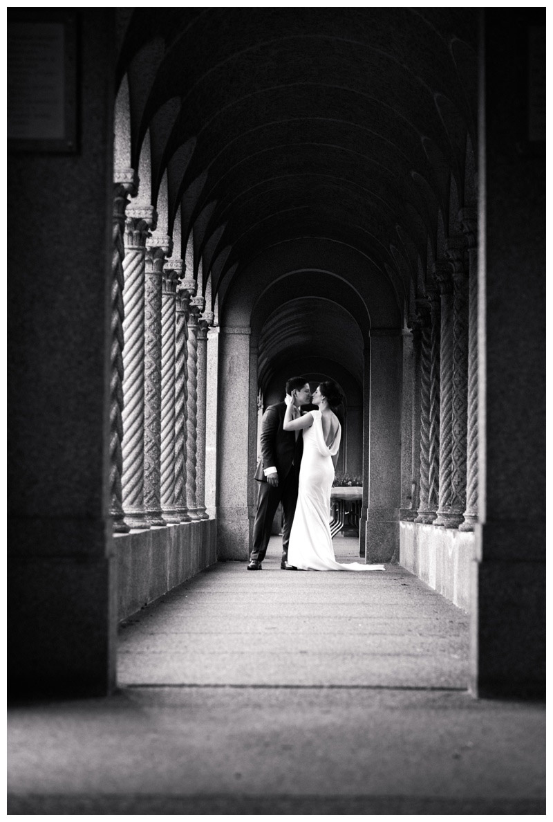 Bride and groom kissing in the archways at St. Francis Monastery in Washington DC. Photographed by Kristen M. Brown, Samba to the Sea Photography.