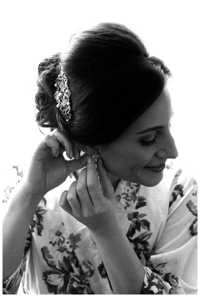 Bride putting on her earrings. Photographed by Kristen M. Brown, Samba to the Sea Photography.