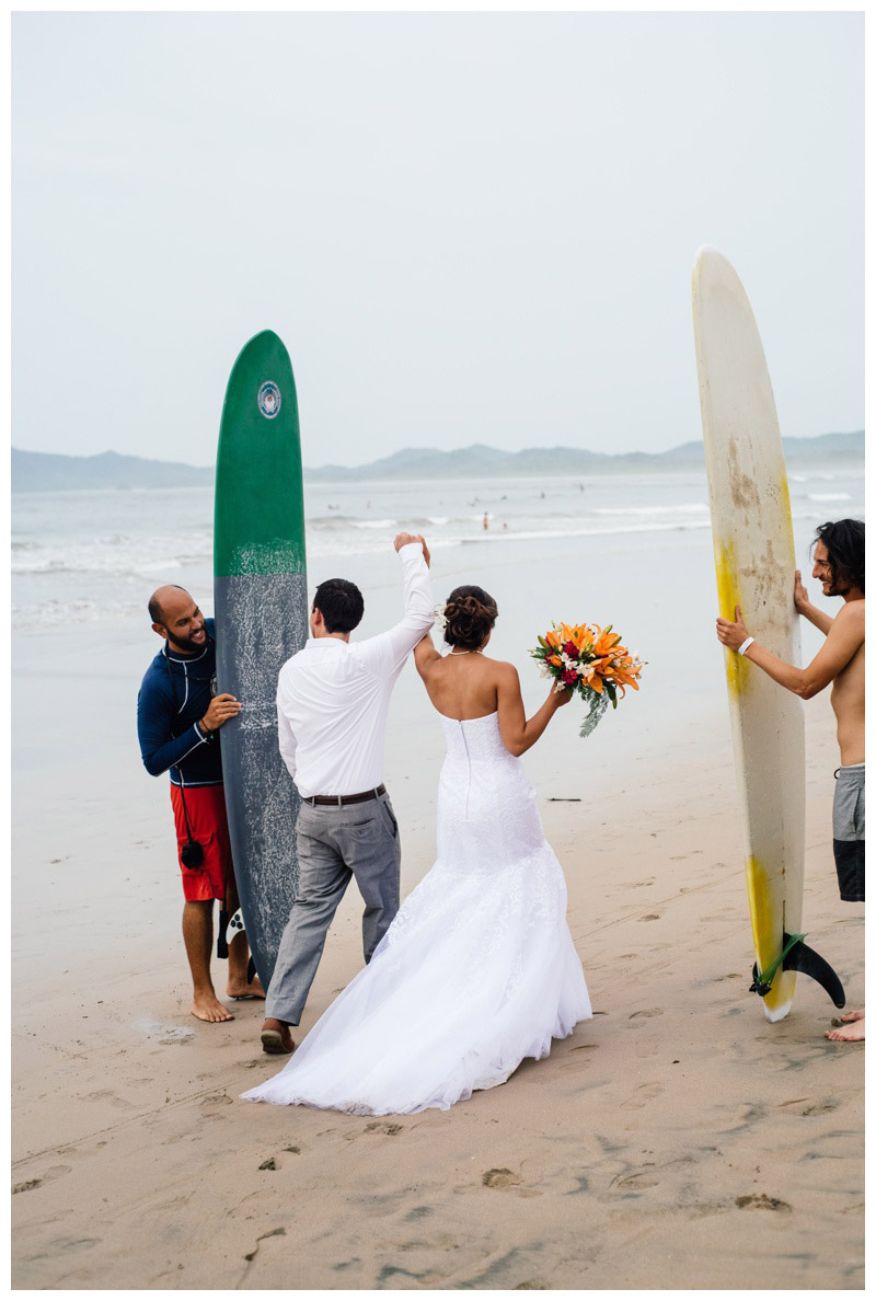 Bride and groom walking through a surfboard arch on the beach in Tamarindo, Costa Rica. Photographed by Kristen M. Brown, Samba to the Sea Photography.