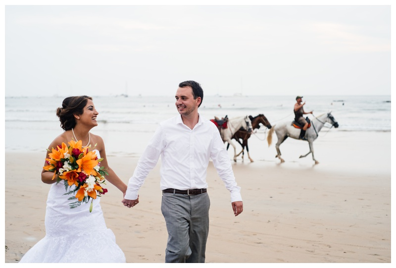Bride and groom walking on the beach in Costa Rica with horses riding on the beach. Photographed by Kristen M. Brown, Samba to the Sea Photography.