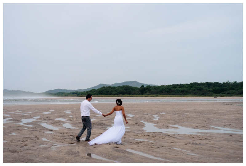 Bride leading her husband and on the beach in Tamarindo, Costa Rica. Photographed by Kristen M. Brown, Samba to the Sea Photography.
