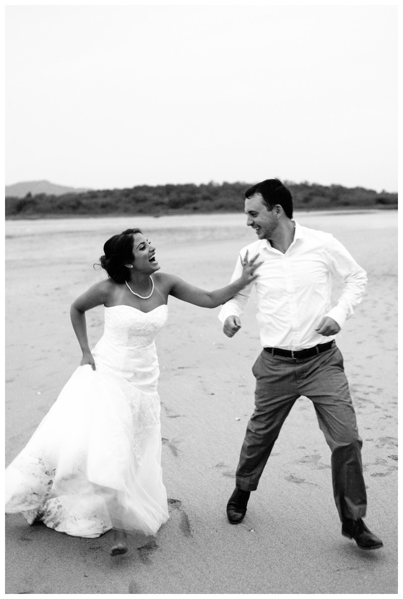 Black and white photo of bride and groom running on the beach after their elopement in Tamarindo. Photographed by Kristen M. Brown, Samba to the Sea Photography.