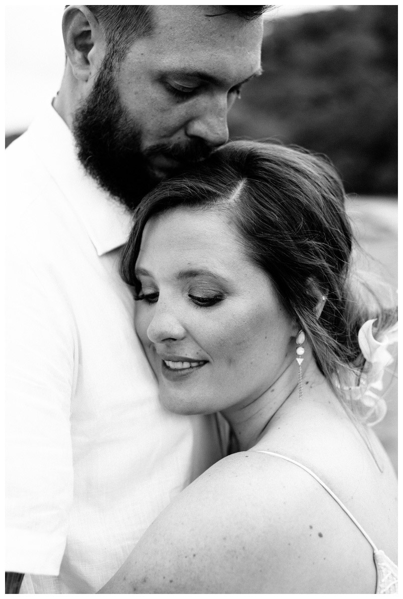 Black and white photo of bride and groom hugging on the beach in Tamarindo Costa Rica. Photographed by Kristen M. Brown, Samba to the Sea Photography.