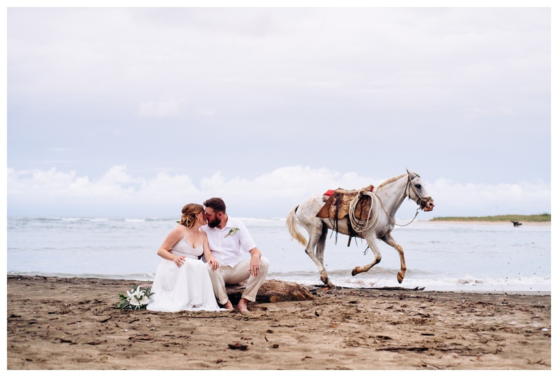 Bride and groom kissing as a white horse runs behind them on the beach in Tamarindo Costa Rica. Bride is wearing a Beautiful Adrienna Papell wedding dress. Photographed by Kristen M. Brown, Samba to the Sea Photography.