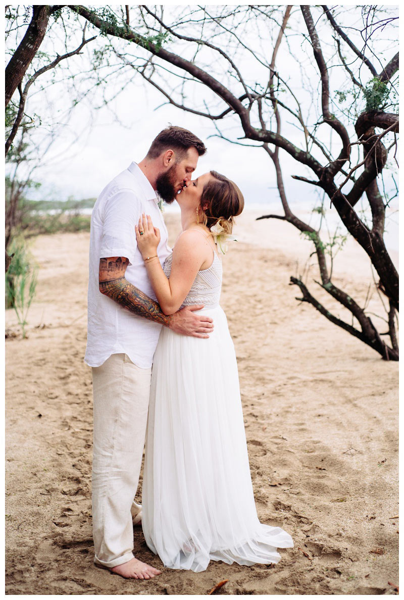 Bride and groom kissing on the beach in Tamarindo Costa Rica. Bride is wearing a Beautiful Adrienna Papell wedding dress. Photographed by Kristen M. Brown, Samba to the Sea Photography.