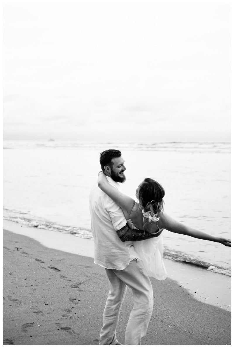 Groom holding bride on the beach in Tamarindo Costa Rica. Photographed by Kristen M. Brown, Samba to the Sea Photography.