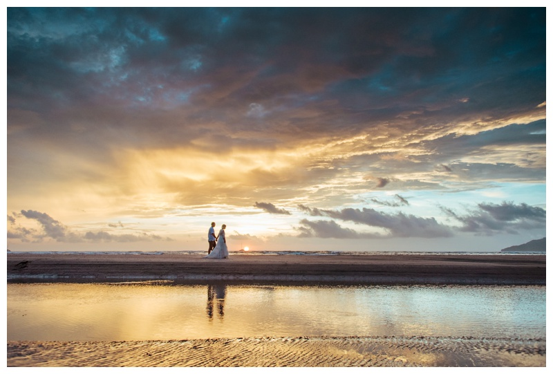 Bride and groom walking on the beach during sunset in Costa Rica. Photographed by Kristen M. Brown, Samba to the Sea Photography.