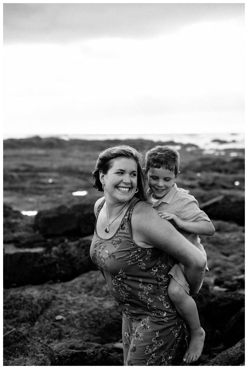Mom giving her son a piggy back ride during family photos in Tamarindo Costa Rica. Photographed by Kristen M. Brown, Samba to the Sea Photography.
