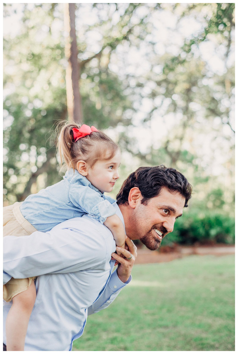 Father giving his daughter a piggy back ride during family photos at The Landings. Photographed by Kristen M. Brown, Samba to the Sea Photography.