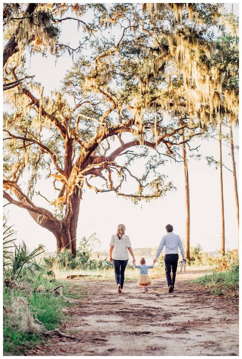 Family walking under a majestic Oak tree during family photos in Savannah. Photographed by Kristen M. Brown, Samba to the Sea Photography.