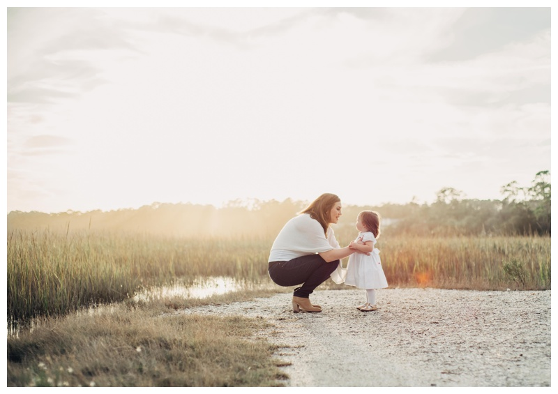Little girl kissing her mom with a beautiful marsh view in the background. Holiday family pictures in Savannah Georgia at The Landings on Skidaway Island. Photographed by Kristen M. Brown, Samba to the Sea Photography.
