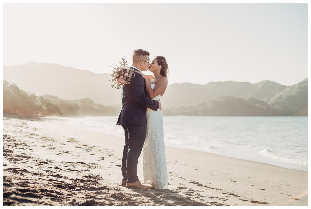 Bride and groom kissing on the beach after their wedding in Costa Rica. Wedding in Guanacaste Costa Rica. Photographed by Kristen M. Brown, Samba to the Sea Photography.