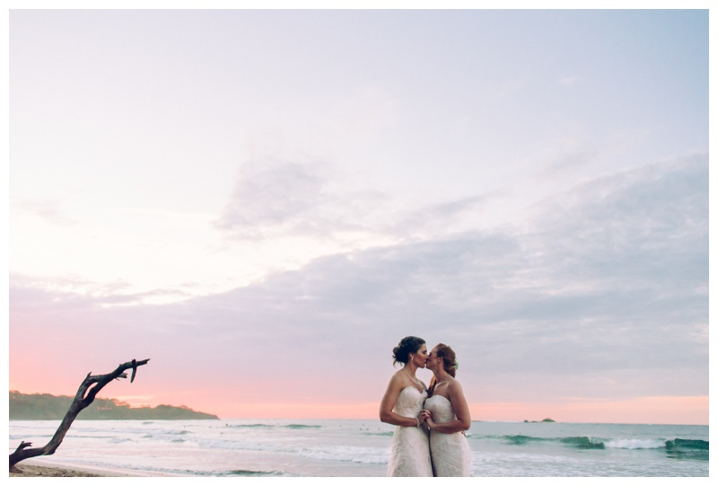 Brides kissing on the beach during sunset in Tamarindo Costa Rica. Photographed by Kristen M. Brown, Samba to the Sea Photography.