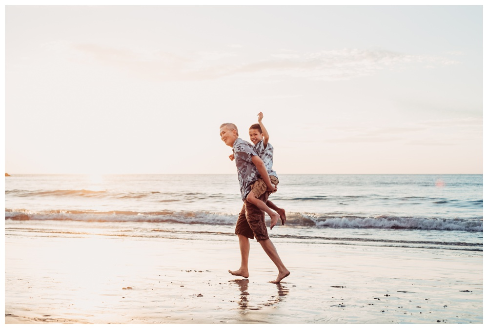 Father giving his son a piggy back ride on the beach in Playa Flamingo Costa Rica. Photographed by Kristen M. Brown, Samba to the Sea Photography.