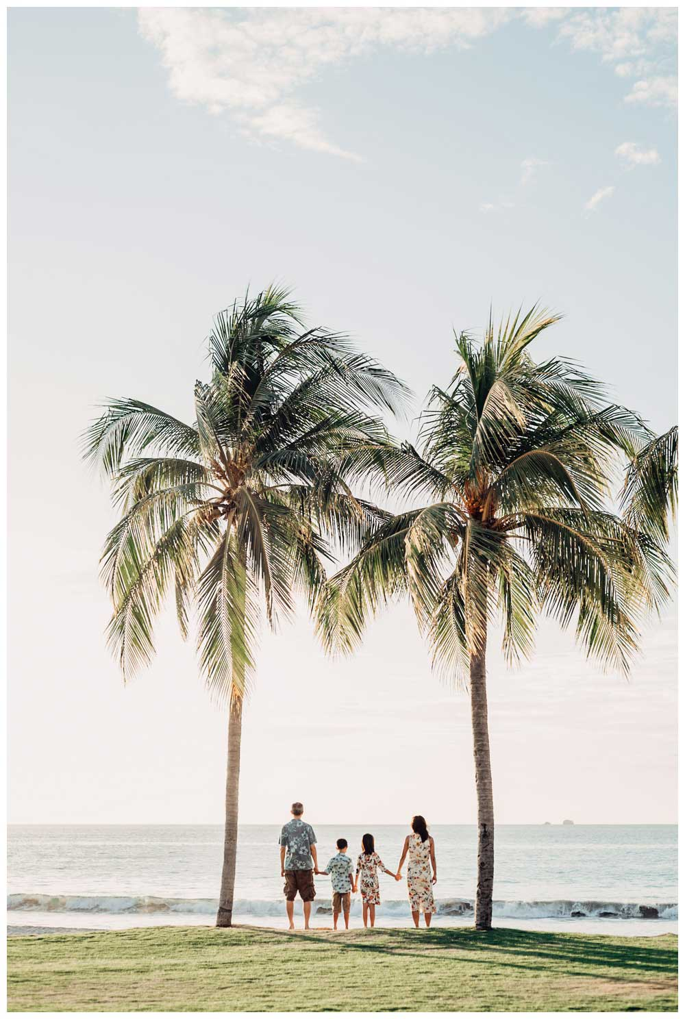 Family standing under palm trees during family photos in Playa Flamingo Costa Rica. Photographed by Kristen M. Brown, Samba to the Sea Photography.