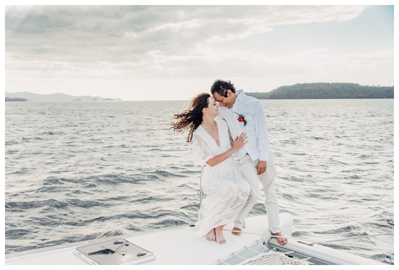 Bride and groom sitting on the sailboat during their magical sailboat elopement in Costa Rica. Photographed by Kristen M. Brown, Samba to the Sea Photography.