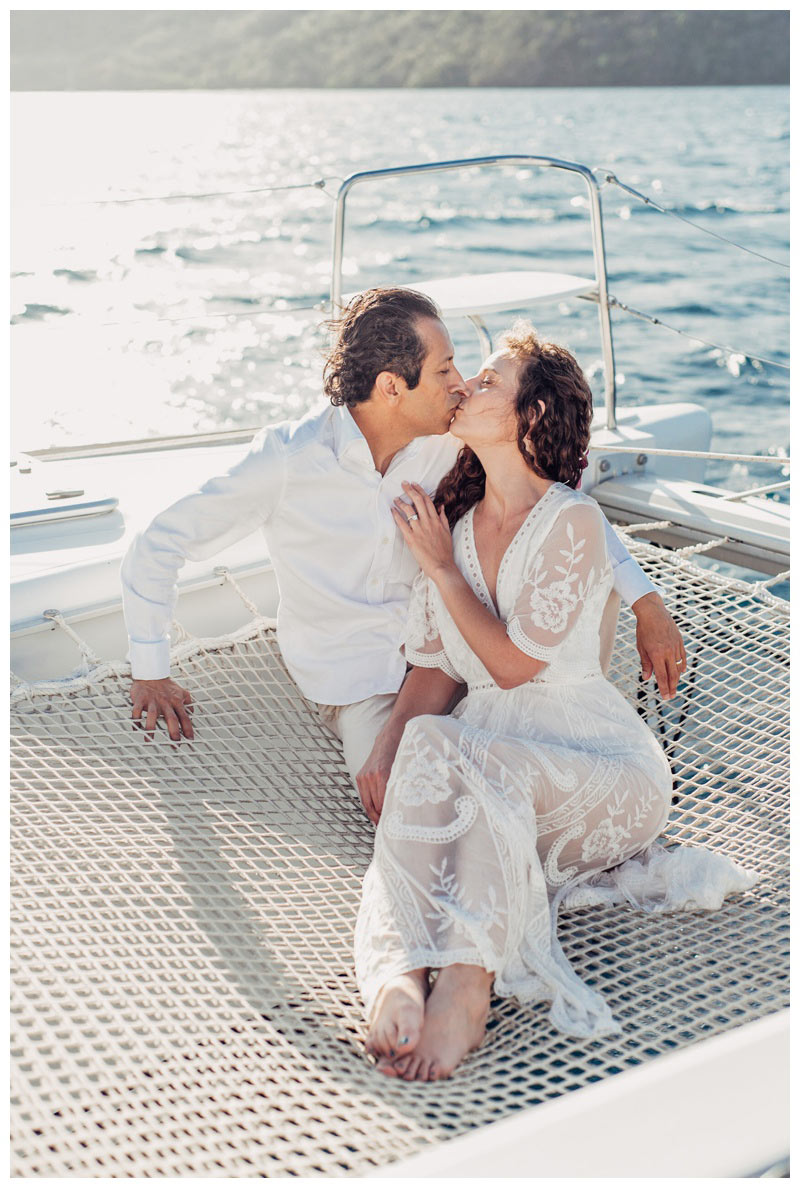 Bride and groom kissing on a sailboat during their magical sailboat elopement in Costa Rica. Photographed by Kristen M. Brown, Samba to the Sea Photography.